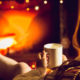 Toned photo of woman warming up with hot tea at fireplace at winter