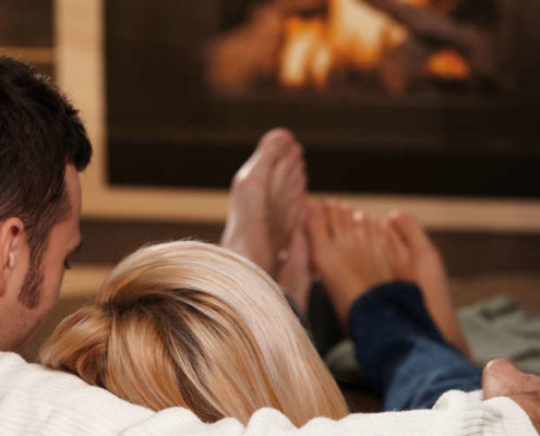 Couple sitting on sofa at home in front of fireplace, rear view.